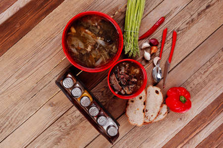 home style beef meat soup vintage country wood table asparagus pepper bell spices bread garlic cutlery spices red bowls