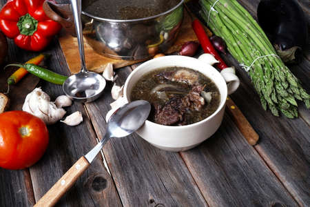 home style beef meat soup vintage country wood table asparagus pepper bell spices bread garlic cutlery eggplant Stock fotó