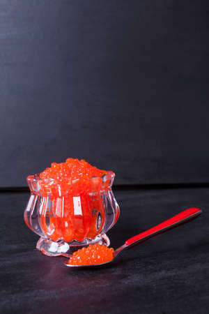 fresh raw red salmon caviar in white crystal bowls with small spoon on blackwooden background Stock fotó