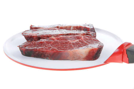 three fresh raw marble beef meat sirloin porterhouse steak on big ceramic cooking pan isolated on white background Stock fotó