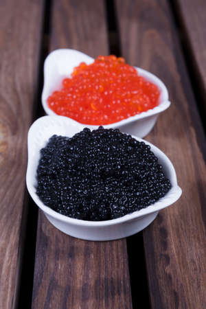 black sturgeon hausen caviar with red salmon caviar in white bowls on wooden background