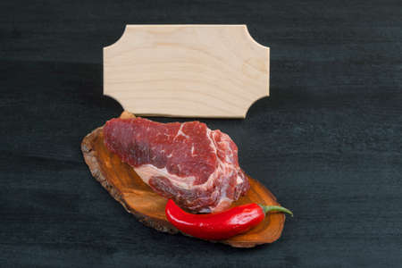 fresh raw piece fillet on small wooden plate with pepper and nameplate space for text on black background Stock fotó