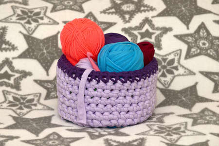 trifles: Handmade basket and colorful yarn. It is crocheted for trifles and decor. Stock Photo