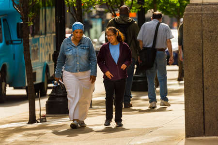 CHICAGO - May 29, 2019: Two women walking and talking on East Jackson Boulevard in Chicago.