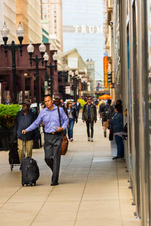 CHICAGO - May 29, 2019: Businessman walking on South Wabash Street in the Chicago Loop. Редакционное
