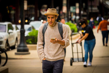 CHICAGO - May 29, 2019: Man walking with a smart phone on West Wabash Avenue in Chicago.