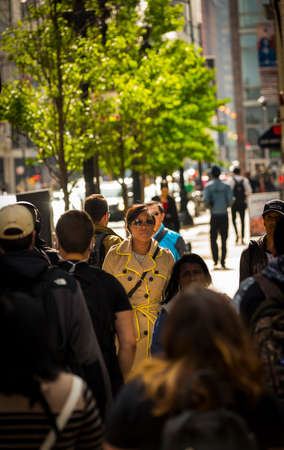 CHICAGO - May 29, 2019: A woman in a crowd of people crossing South Wabash Avenue in Chicago.