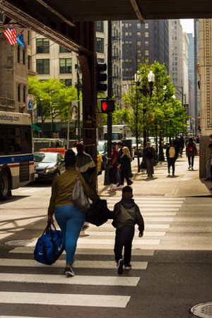 CHICAGO - May 29, 2019: A woman and child crossing South Wabash Avenue in Chicago.