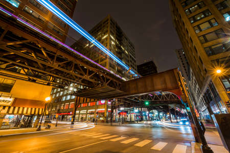 An L train runs over West Monroe Street and South Wabash Avenue. Редакционное