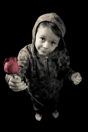 forgive: Young boy giving a red rose  Stock Photo