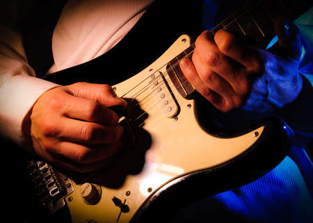 strat: close up of a mans hands playing a guitar,
