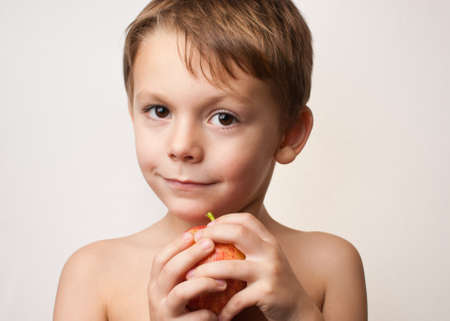 young child holding an apple on a white background photo