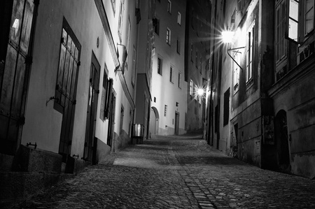 A black and white of a dark European alleyway at night in horizontal