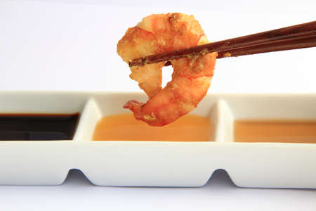 chopstick holding a prawn and dipping sauces