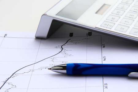 bearish: bearish stock chart with calculator and blue pen Stock Photo
