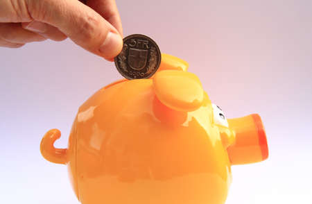 hand inserting a coin in yellow pig moneybox photo