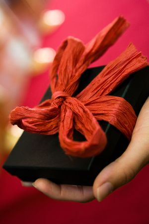 A womans hand holding a beautifully wrapped black box Stock Photo