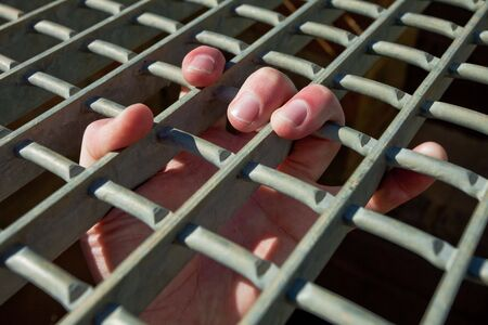 A mans fingers holding on to the bars of a cage or jail Stock Photo