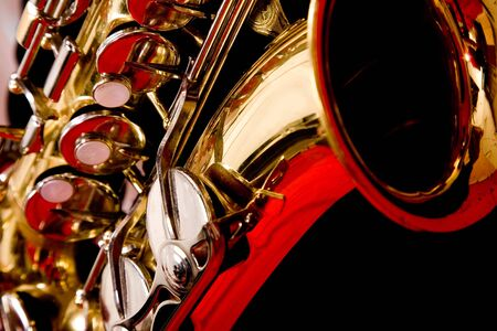 Close up of a Saxaphone against a red background