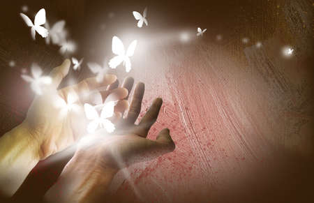 Graphic illustration composed of two hands setting butterflies off into free flight with abstract brush strokes on textured background Stock Photo