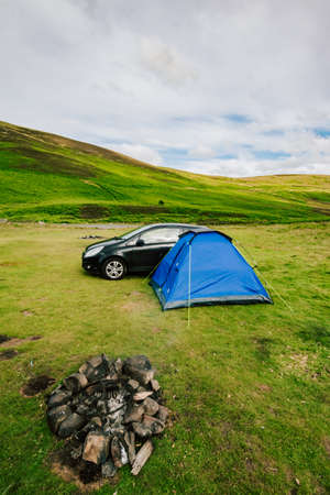 Wild camping in a tent with car and fire