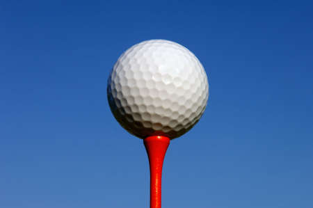 Golfball on red tee against blue sky