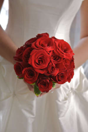 close up of bride holding bouquet of red roses
