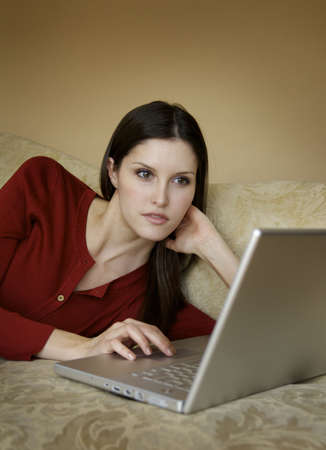 Attractive girl on couch with laptop Stock Photo