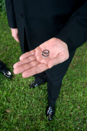 Close up view of a groom holding wedding rings in hand