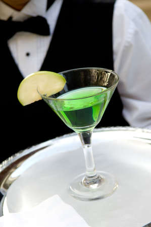 image of an apple martini drink with an apple garnish being served