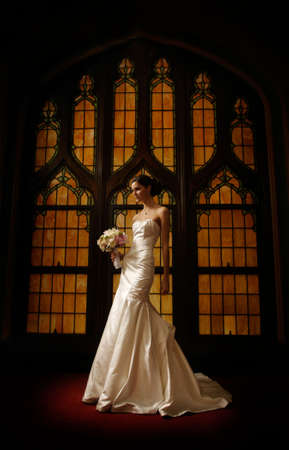 image of bride in front of a stained glass window on a step holding bouquet of flowers in one hand photo