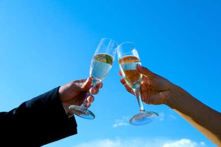 Bride and groom toasting against sky
