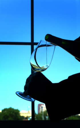 Wine being poured silhouetted against window