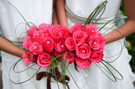 An image of bridesmaids holding virbrant pink rose bouquets