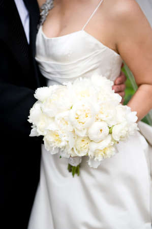 An image of a bride holding her bouquet wit her groom Stock Photo