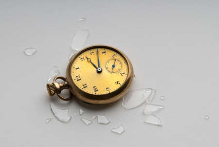 Close-up image of an antique gold watch with shattered crystal photo