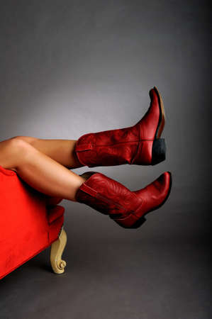 Image of a pair of legs hanging off a red chair wearing red cowboy boots