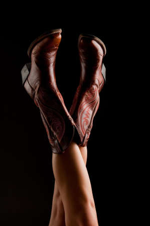 Image of a pair of legs in the air wearing cowboy boots