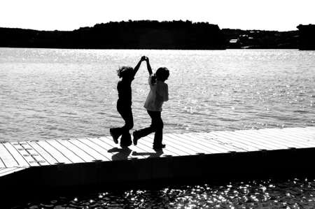 pier: Image of a silhouette of two young girls playing on a dock