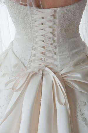 Close-up beeld van de gedetailleerde veters op de rug van een trouw jurk