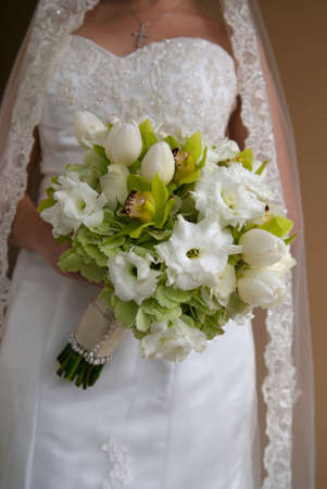 Image of a bride from the neck down holding bouquet of white and green flowers