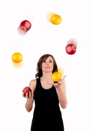 Beautiful woman juggling apples and oranges in motion a white background photo