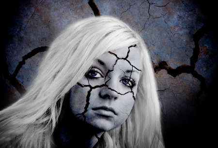 Image of a beautiful young girl with a fractured  cracked face. A very striking image with graphic impact photo