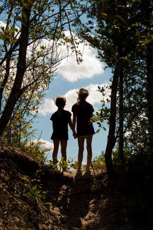 ni�os caminando: Imagen de dos chicas j�venes manos, de pie sobre un trazado en la cresta de una colina, mirando en la distancia.  Foto de archivo