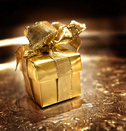 Image of a small gold giftwrapped box with ribbon on a silver tray Stock Photo