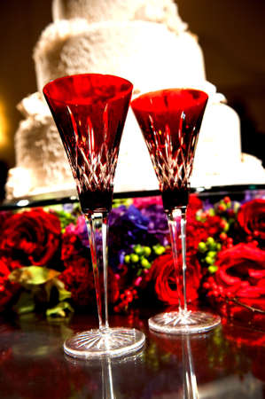 Image of 2 beautiful red champagne toasting flutes by the cake at a wedding