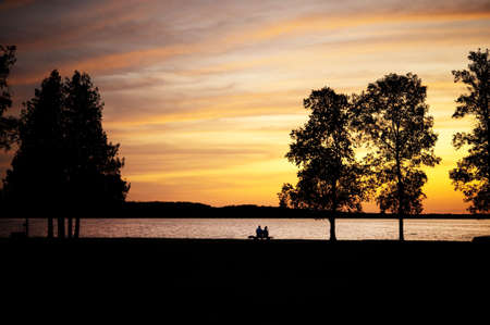 Elderly couple, silhouetted,  sitting on a bench by lake at sunset Stock Photo