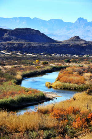 Image of winding stream in front of mountain range
