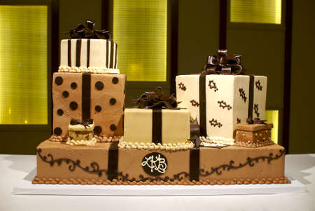 Image of a brown and white wedding cake with multiple layers, polka dots, and stripes