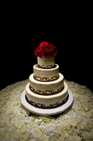 Image of a traditional four tiered wedding cake with red roses on top sitting on a bed of white roses Stock Photo